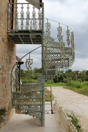 The stencil steel spiral staircase outside of the house.