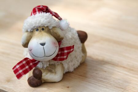 The smile teddy sheep on the wooden table.
