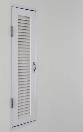 White small wooden louver door on white concrete wall. 版權商用圖片