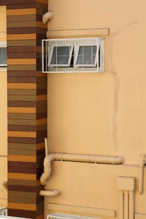 Ventilation windows on orange concrete wall.