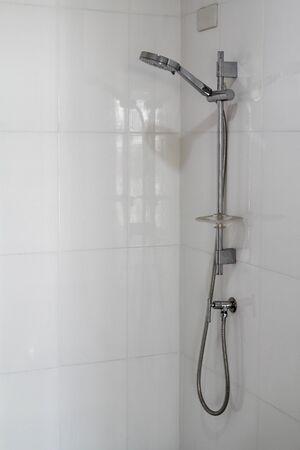 Soffione doccia moderno sulla parete bianca in bagno.
