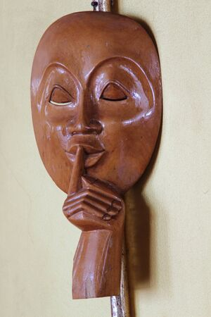 Be quiet please! close up of man face wood carving on white background.