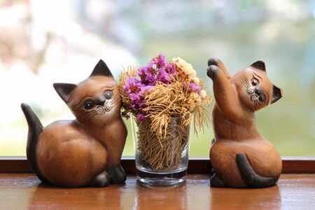 Ceramic cats with flower pot on wooden table. 写真素材
