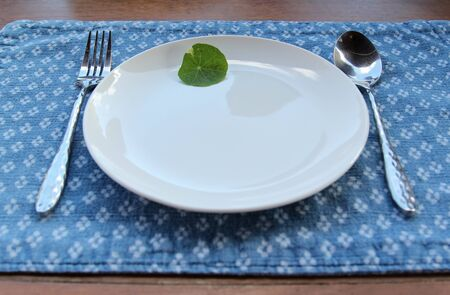 A small green leaves decorated on a white ceramic plate with spoon and fork on blue placemat. Archivio Fotografico - 142673291