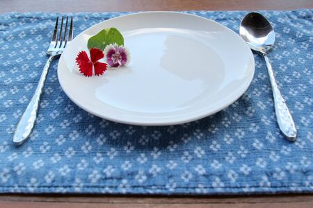 A small green leaves and flowers decorated on a white ceramic plate with spoon and fork on blue placemat. Archivio Fotografico - 142673163