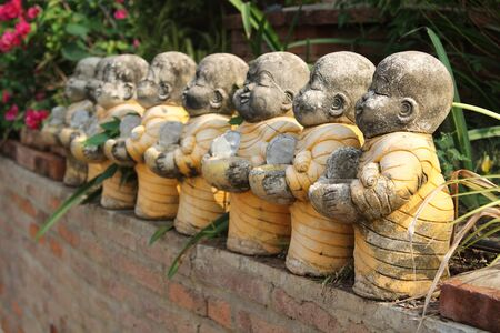 Row of old clay doll novice on brick wall in Thai temple. Stock Photo