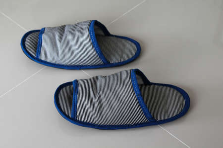 Casual shoes or Slippers for home use on the grey floor tiles.