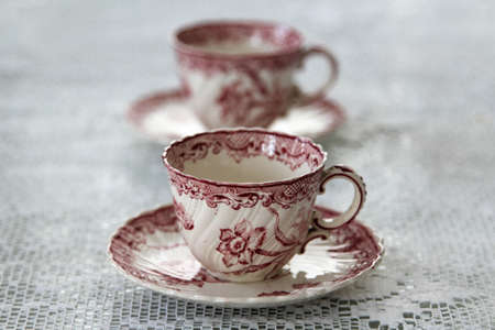 White ceramic coffee cup with pink flower pattern on the table.