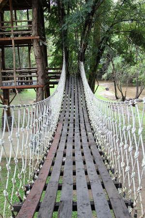 Suspension bridge across green grass on rainy days.