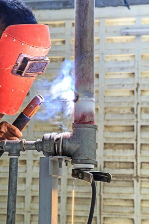 protective: Worker with protective mask sparks piping welding