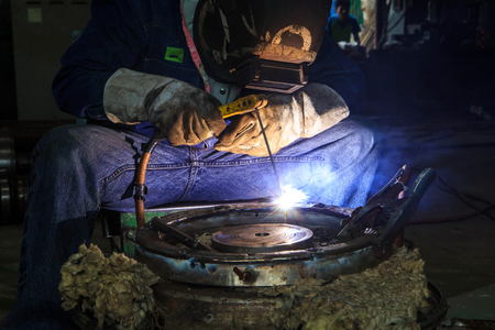 skilled labour: Worker with protective mask sparks piping welding
