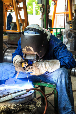 protective mask: Worker with protective mask sparks piping welding