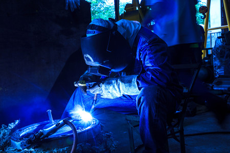 laboring: Worker with protective mask sparks piping welding