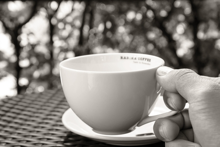 White coffee cup placed on the table sill.