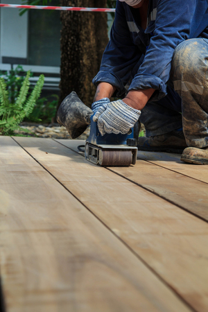 Carpenter working with electric planer on wooden plank outdoor. Stock Photo