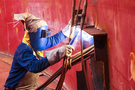 Male  worker wearing protective clothing and repair welding industrial construction oil and gas or  storage tank inside confined spaces. Imagens