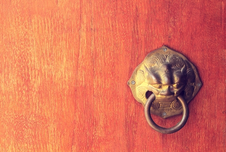 Old wooden door decorated with a lion head as a knocker