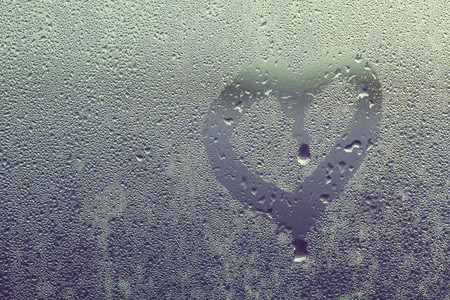 Steam on glass caused by moisture and heart-shaped background.