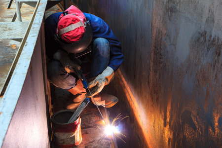Male  worker wearing protective clothing and repair welding industrial construction oil and gas or  storage tank inside confined spaces. Stock Photo