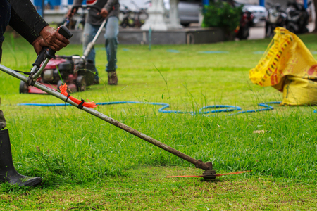 Man worker cutting grass with at the lawn.