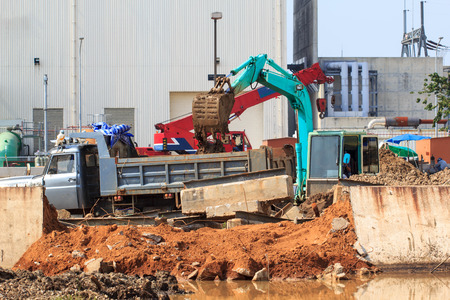 Green excavator against construction site or demolition site of power plant