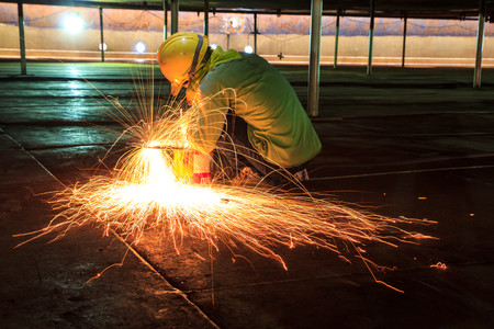 Male  worker wearing protective clothing and Cutting sparks  industrial construction oil and gas or  storage tank inside confined spaces.
