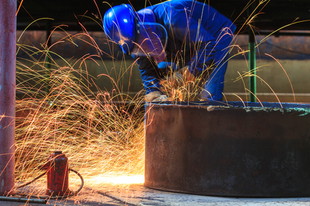Male  worker wearing protective clothing and repair grinding industrial construction oil and gas or  storage tank inside confined spaces.