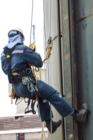 Bangkok Thailand - September 10th, 2016: Male worker rope access  inspection of thickness storage tank industry.