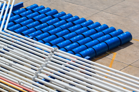 pipeline oil and gas production petroleum refinery oil barrels or chemical drums stacked up Stock Photo