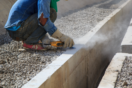 Builder worker with grinder machine polished finishing concrete drain water at construction site Stock Photo