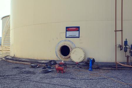 botola arrugginita aperta sul serbatoio del carburante bianco e aria fresca del ventilatore nello spazio limitato del serbatoio di stoccaggio dell'olio