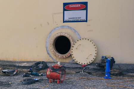 opened rusty manhole on the white fuel tank and blower fresh air into oil storage tank confined space Stock Photo
