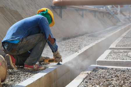 Builder worker with grinder machine polished finishing concrete drain water at construction site 版權商用圖片