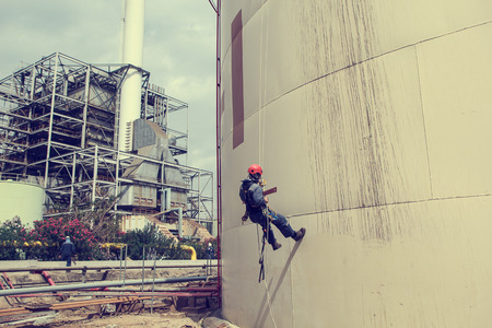 Male worker rope access  inspection of bending the curve storage tank industry.