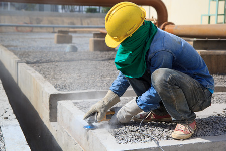Builder worker with grinder machine polished finishing concrete drain water at construction site