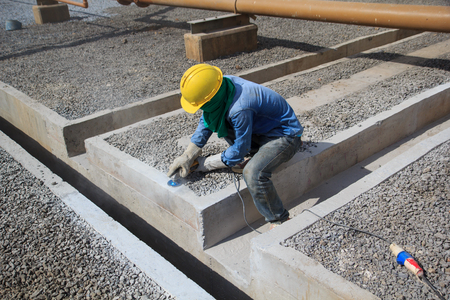 Builder worker with grinder machine polished finishing concrete drain water at construction site Reklamní fotografie