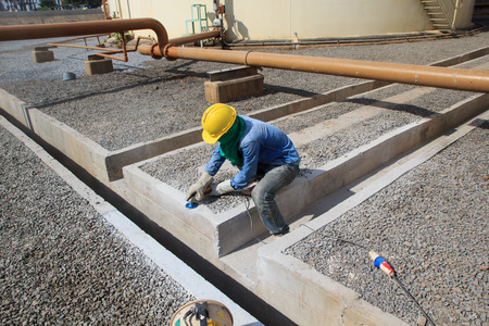 Builder worker with grinder machine polished finishing concrete drain water at construction site Reklamní fotografie