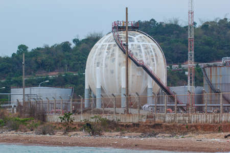 Spherical tanks containing fuel gas oil refineries next to the sea. 版權商用圖片