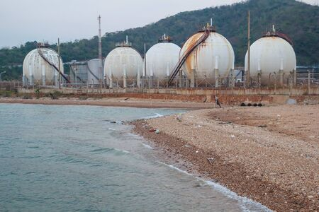 Spherical tanks containing fuel gas oil refineries next to the sea. Banco de Imagens
