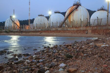 Spherical tanks containing fuel gas oil refineries next to the sea. Stock Photo