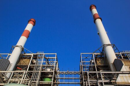 Smokestack in power plant with blue sky and clouds