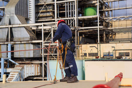 Male worker standing on tank roof  before working safety on rope access of inspection storage tank