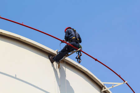 Male worker sitting on fire water tube rope access of inspection storage tank Standard-Bild