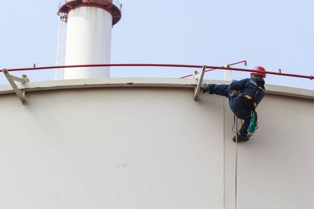 Male worker is stepping down from the tank to at the rope access inspector thickness of storage tank oil Banco de Imagens - 129735721