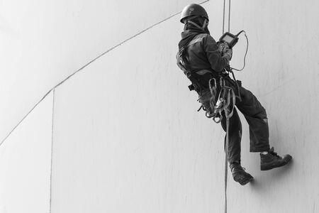 Inspección de acceso por cuerda de trabajador masculino monocromo de la industria del tanque de almacenamiento de espesor.