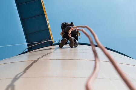 Male worker rope access  inspection photo from the bottom of the fuel tanks.