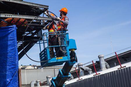Dos trabajadores masculinos de la industria en una plataforma elevadora trabajando en alto Instale el cable de alimentación. Foto de archivo