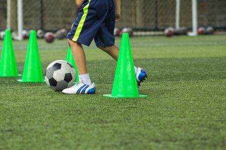 Tattiche di pallone da calcio sul campo in erba con cono per l'allenamento della thailandia in background Formazione dei bambini nell'accademia di calcio