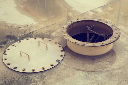 Opened rusty manhole on the white fuel tank roof deck storage tank confined space