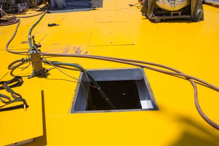 opened rusty manhole on the yellow platfrom offshore confined space